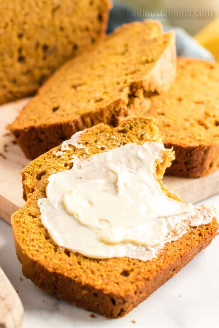 close up of a buttered slice of pumpkin banana bread with a bite taken out