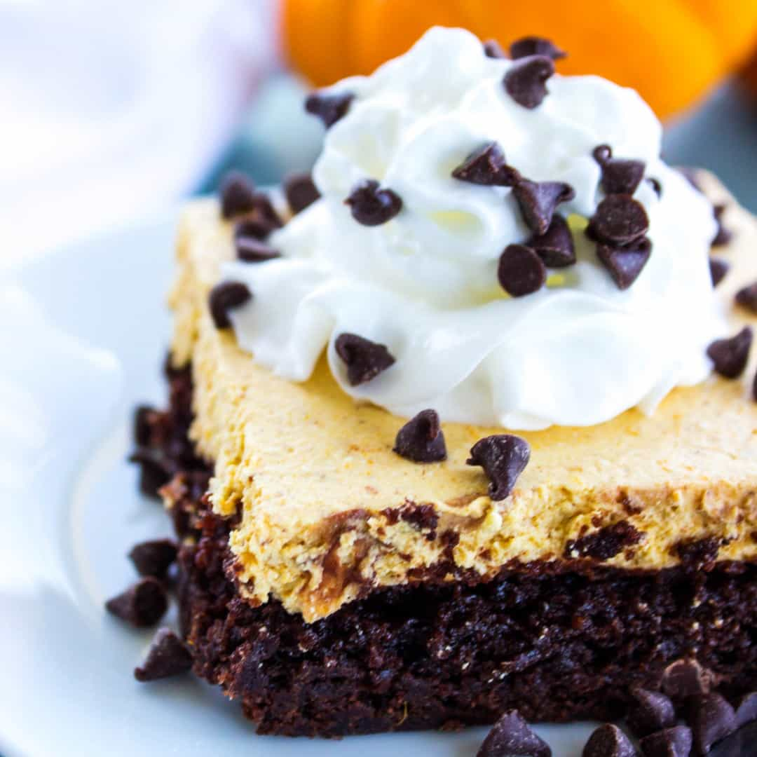 Pumpkin Cheesecake Brownie Bars are topped with a pumpkin no-bake cheesecake then finished off with whipped topping and mini chocolate chips. This is an easy fall must-have!