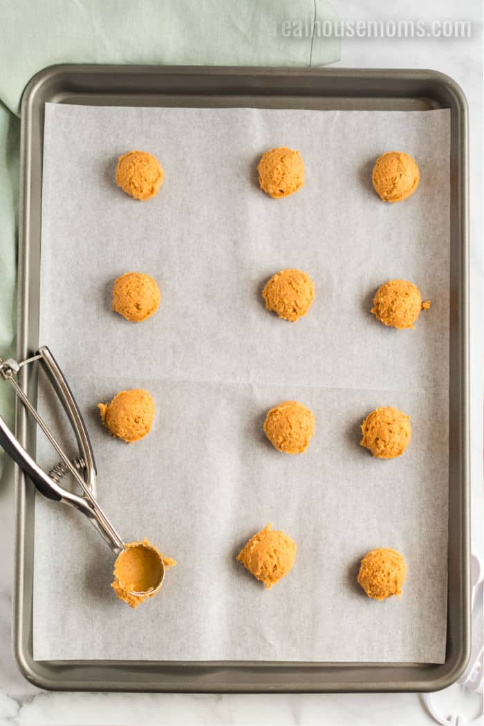a cookie scoop next to scoops of pumpkin cookie dough on a bakgin sheet with parchment paper