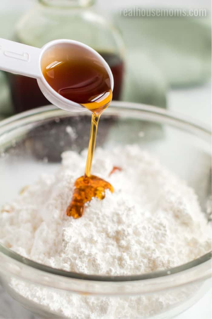 aple syrup being poured over a bowl of powdered sugar