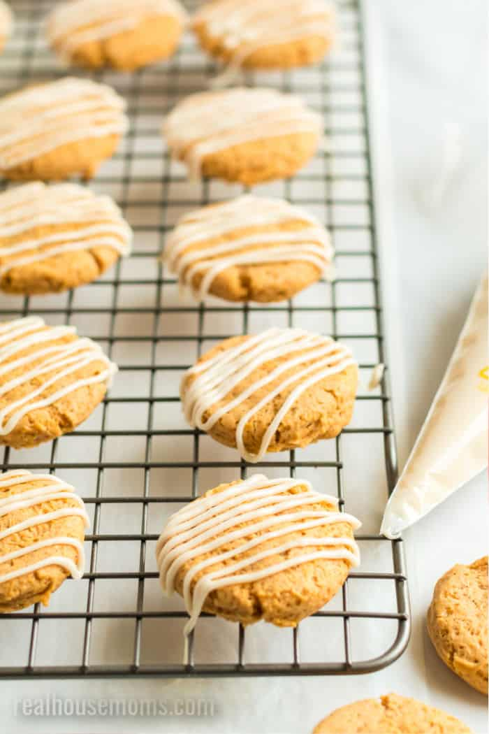 baked pumpkin cookies with marple frosting drizzled over top on a wire rack next to a piping bag