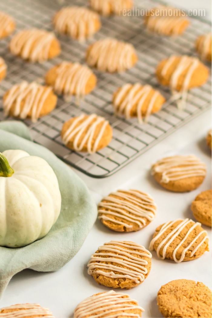 maple frosting pumpkin cookies on a cooling rack and on the counter next to a small white pumpkin