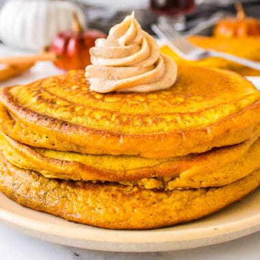 square image of pumpkin pancakes stacked with pumpkin spice butter on top
