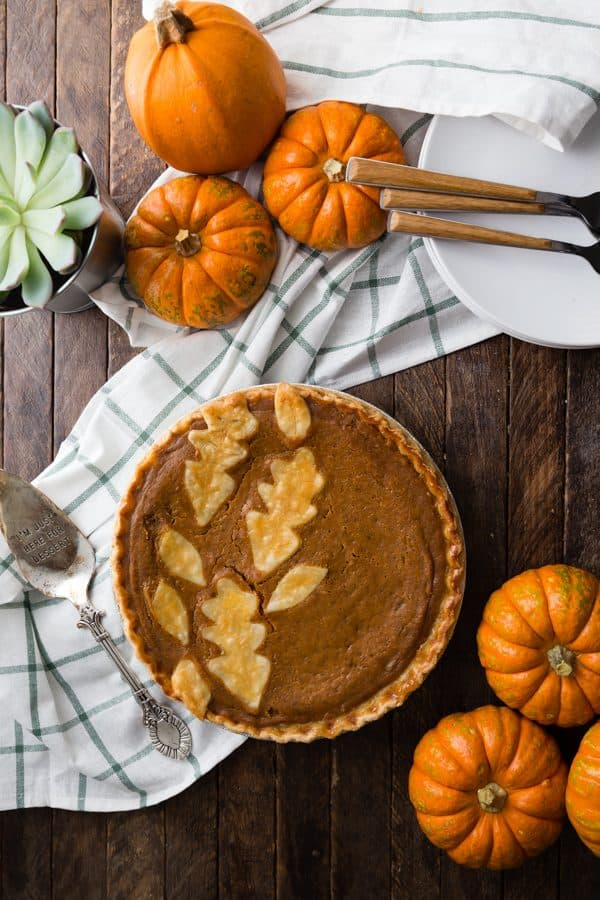 Best Pumpkin Pie Recipe placed on a dessert table with a serving utensil, small pumpkins, serving plates and forks