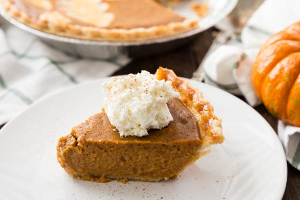 A slice of the best pumpkin pie recipe topped with whipped cream and a sprinkle of cinnamon