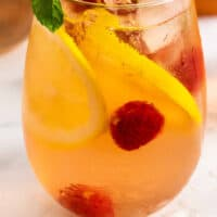 raspberry lemonade moscato sangria in a stem less wine glass with recipe name at bottom
