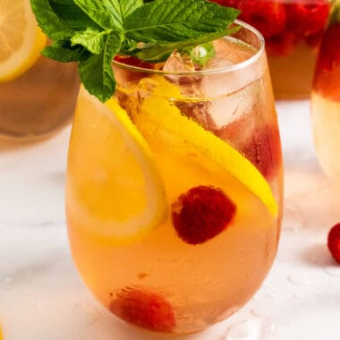 square image of Raspberry Lemonade Moscato Sangria in a stemless wine glass with fruit garnish