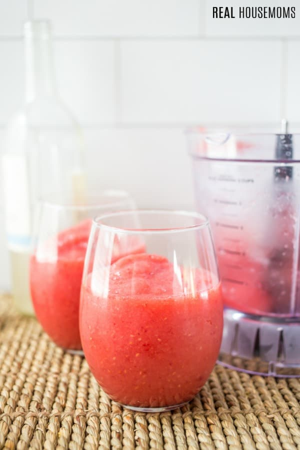 blender with raspberry peach wine slushie and wine glasses