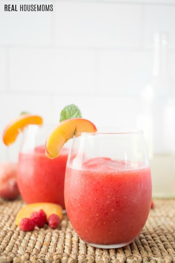 raspberry peach wine slushies in stemless wine glasses