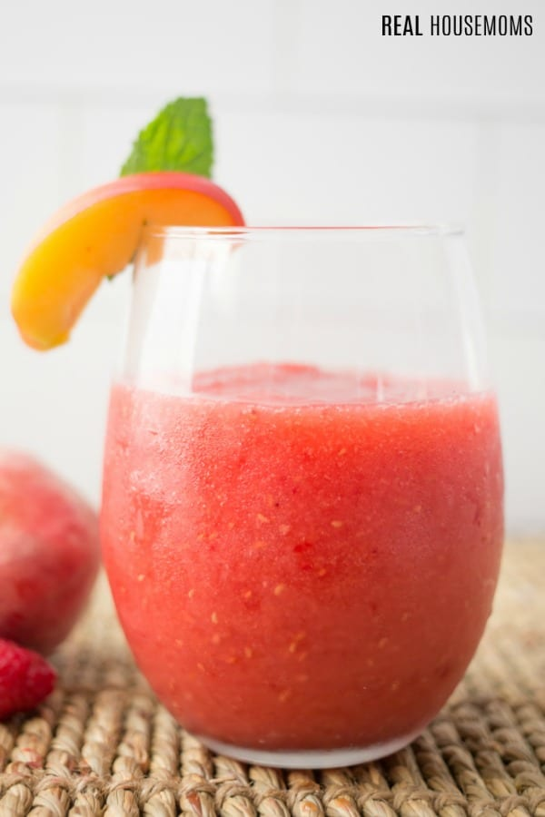 close up of raspberry peach wine slushie in a stemless wine glass