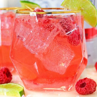 square image close up of raspberry white claw cocktail with limes and raspberries
