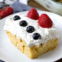 Red, White and Blue Cheesecake Poke Cake is a super easy dessert recipe that is perfect for celebrating the Fourth of July!