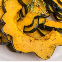 sliced roasted acorn squash with a sprig of fresh thyme on a plate with recipe name at the bottom