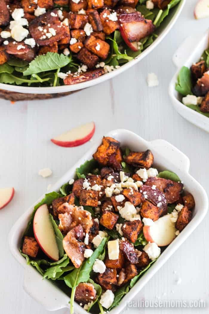 top view of roasted sweet potato salad , with a big white bowl of salad and a small serving bowl of salad