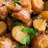 close up of a spoonful in rosemary & garlic instant pot potatoes over a bowl with recipe name at the bottom
