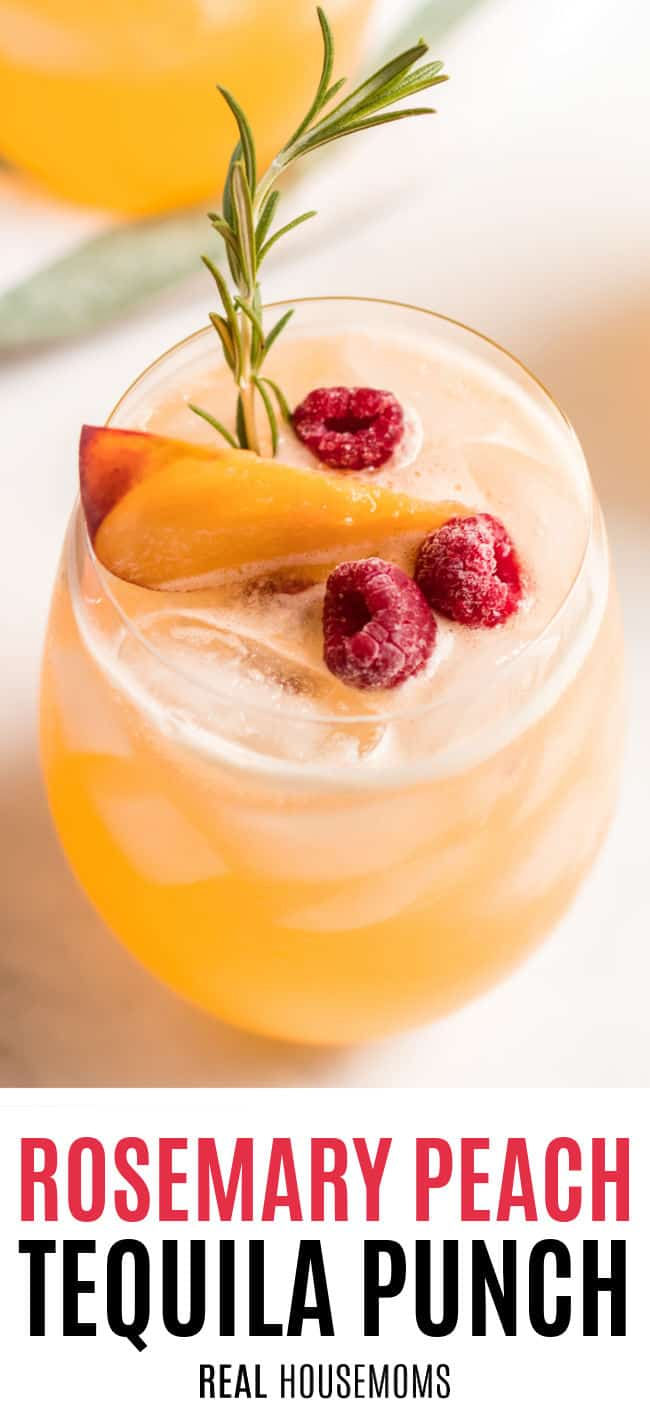 glass of rosemary peach tequila punch garnished with rosemary, sliced peaches, and raspberries