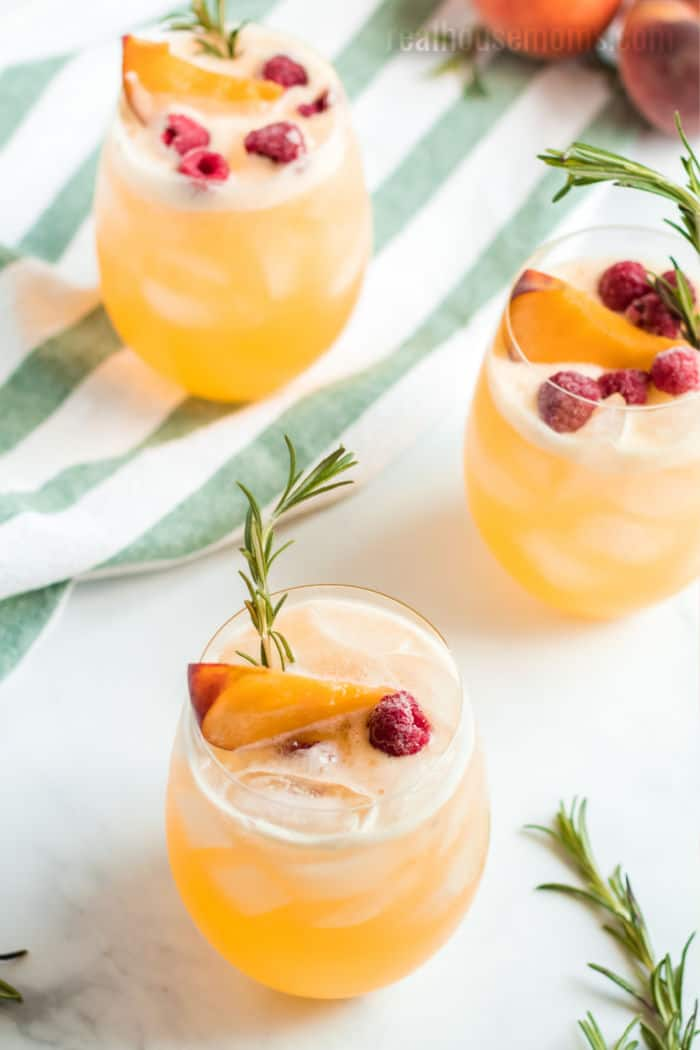 three glasses of tequila peach punch with peaches and raspberries