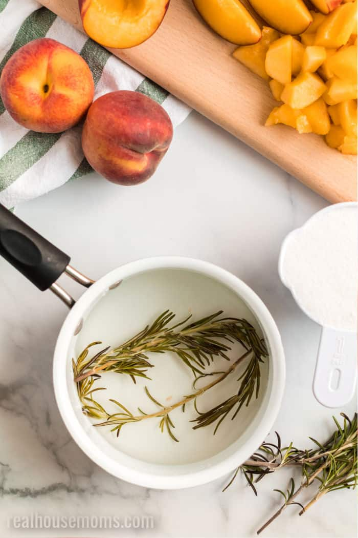rosemary steeping in simple syrup in a saucepan next to whole and sliced peaches