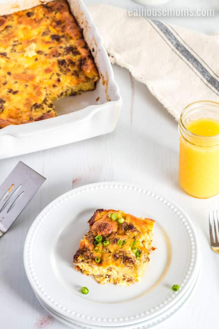 breakfast casserole on a plate with orange juice