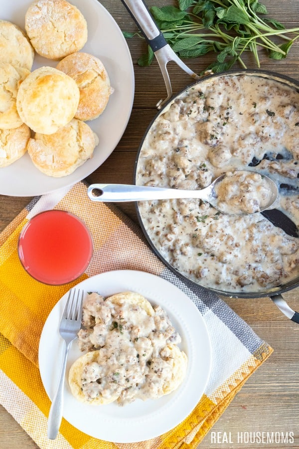 overhead picture of sausage gravy with a plate of biscuits and biscuits & gravy