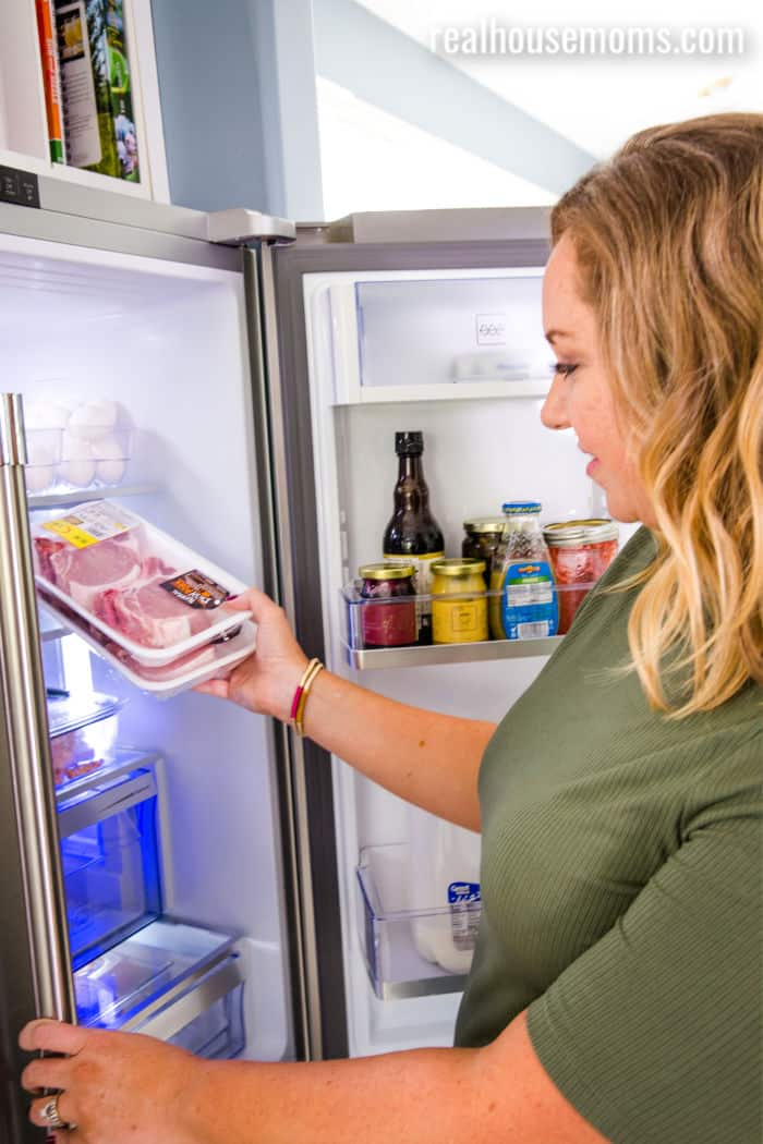woman taking pack of pork chops out of fridge