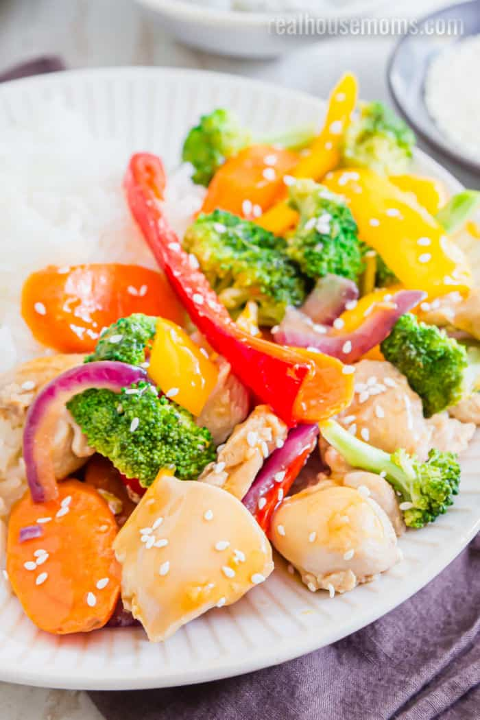 close up of chicken and vegetables with orange teryaki sauce on a plate sprinkled with sesame seeds