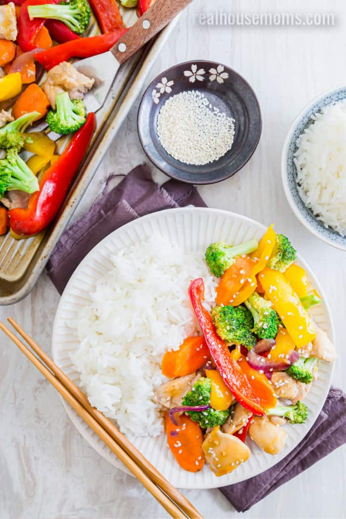 teriyaki chicken and vegetables on a dinner plate with cooked white rice and chopsticks next to the sheet pan with more chicken and vegetables