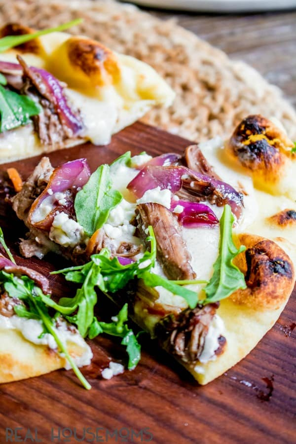 A slice of Short Rib Naan Pizza pulled away from the full pizza