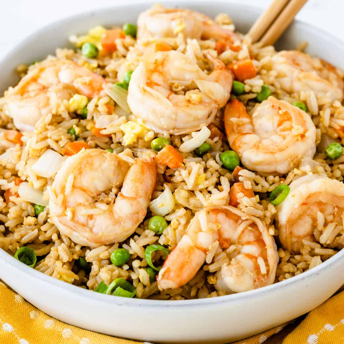 square image of shrimp fried rice in a bowl with chopsticks