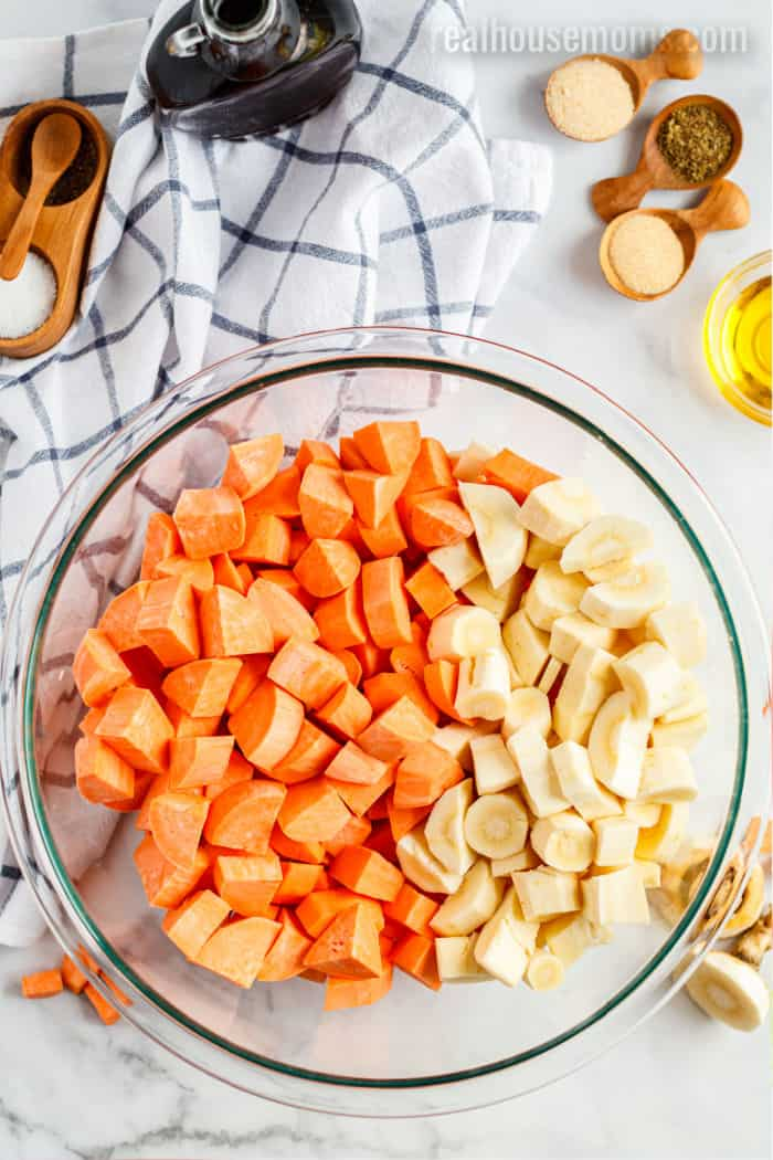 chopped root vegetables in a mixing bowl next to bowls of spices and oil