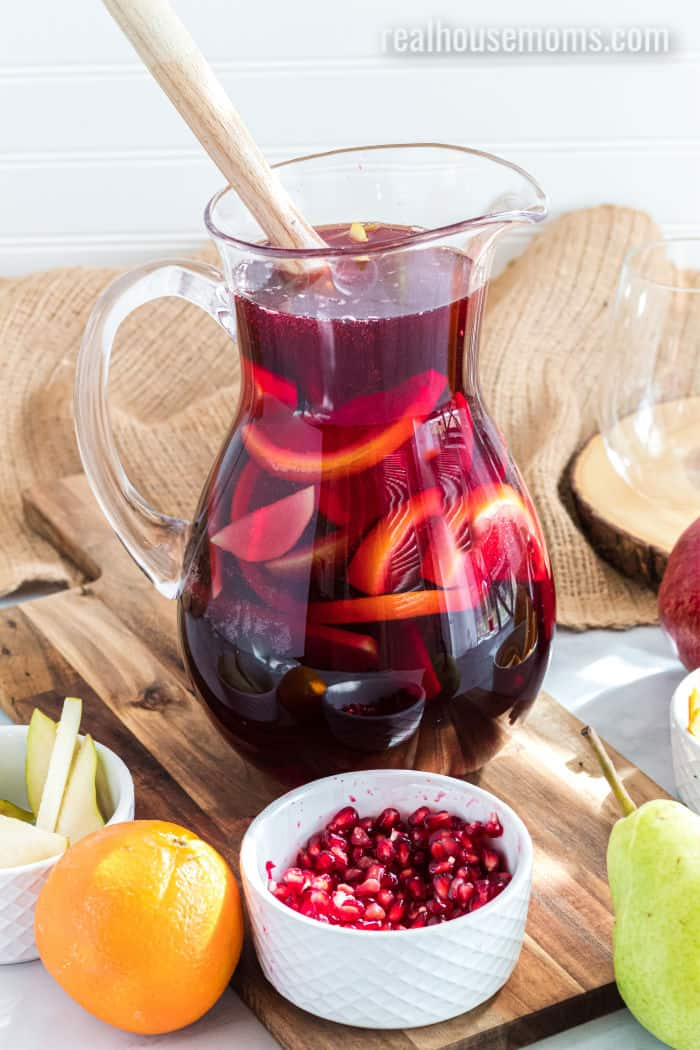 pitcher of red sangria with fruit and a wooden spoon