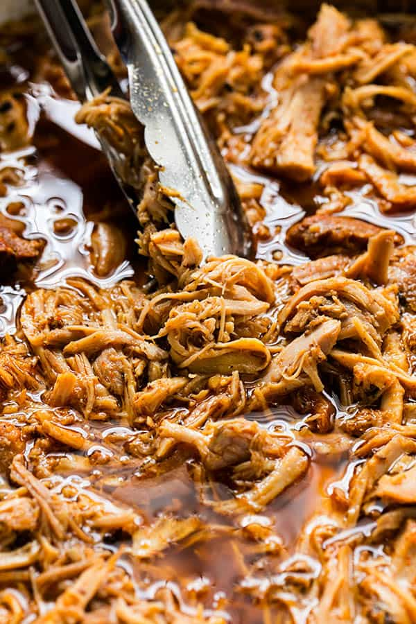 Finished Slow Cooker Cherry Cola Pulled Pork in the crock pot with tongs lifting some of the pork out of its juices