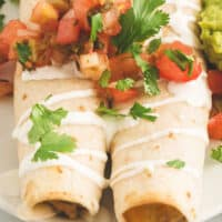 close up of two slow cooker chicken taquitos on a plate with recipe name at bottom