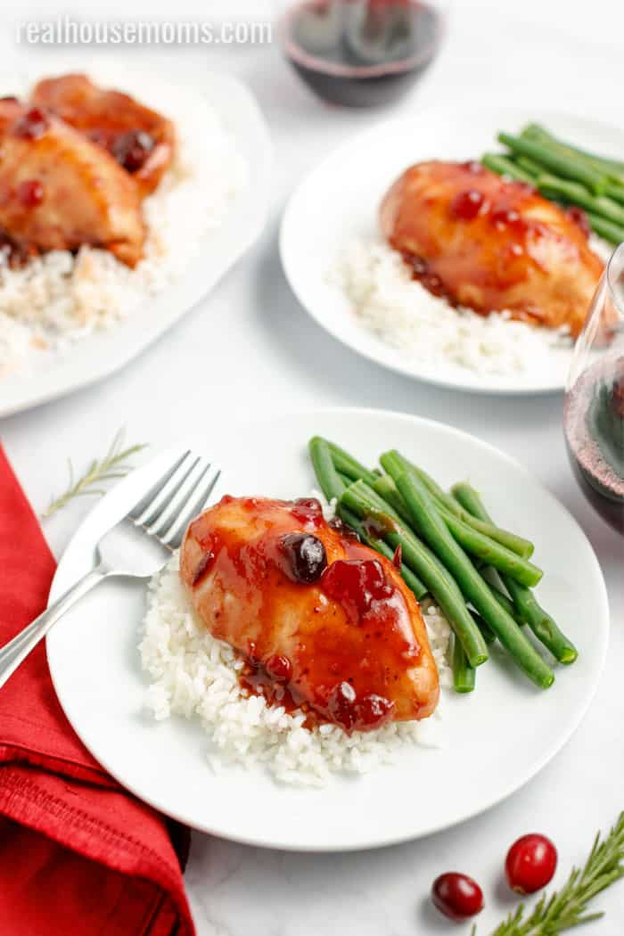 slow cooker cranberry chicken over rice with green beans on a plate