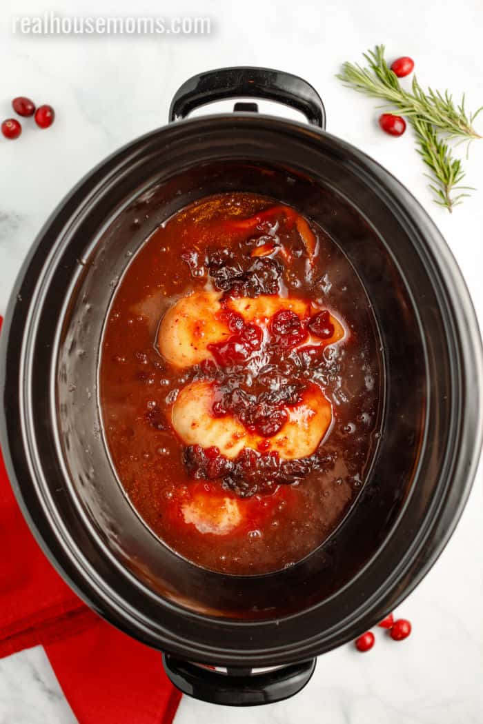 cooked cranberry chicken in a slow cooker