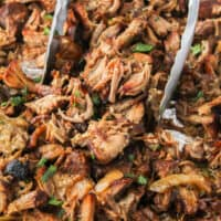 square image of slow cooker carnitas with tongs picking some up