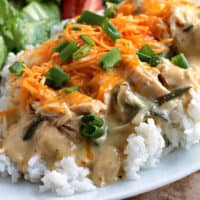 square image of Slow Cooker Poblano Chicken over rice with cheese and green onions on top