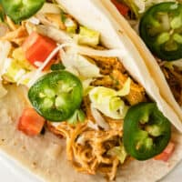 close up of slow cooke queso chicken tacos with recipe name at bottom