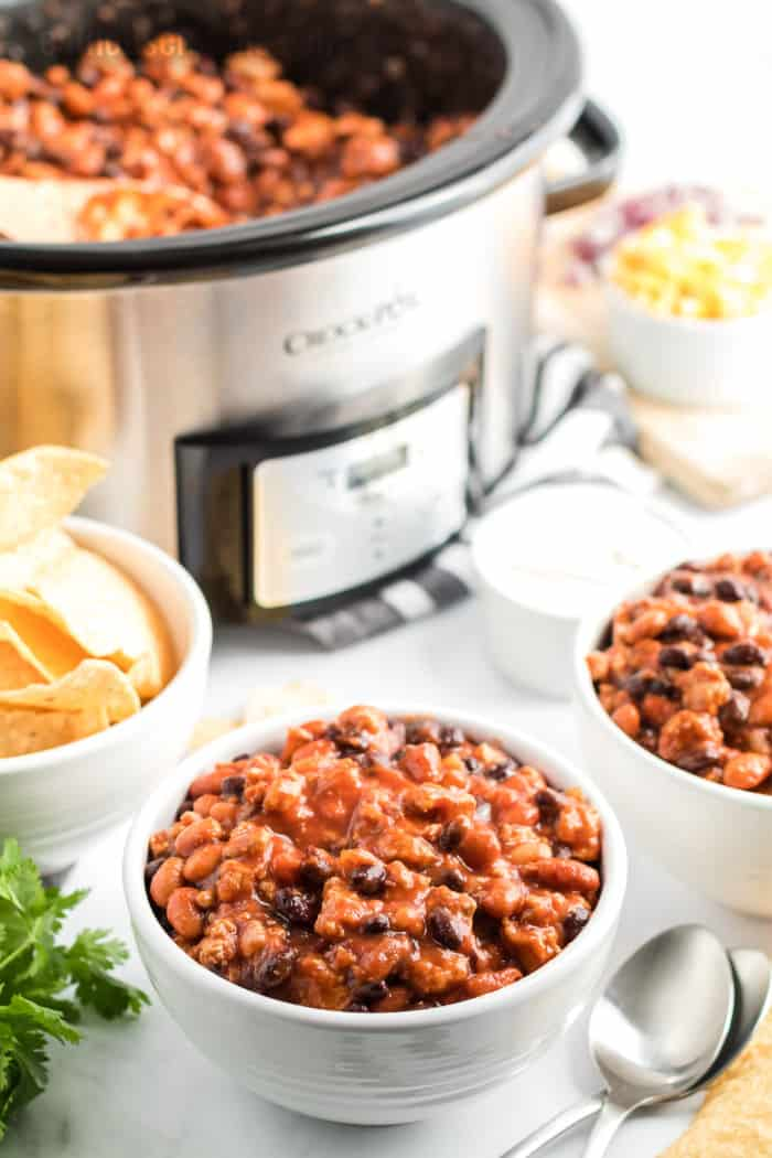 two bowls of chili next to a slow cooker