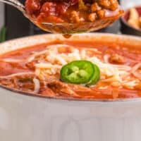 spoonful of wendy's chili over a bowl in front of a slow cooker with recipe name at bottom