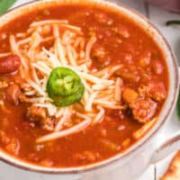 square image of slow cooker wendy's chili in bowl topped with shredded white cheddar cheese and jalapeno slices