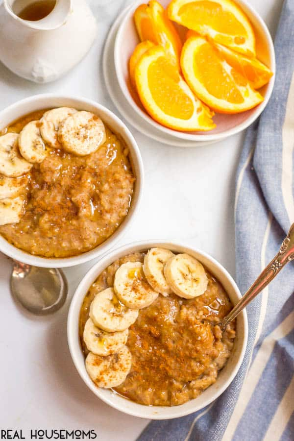 Two bowls of Slow Cooker Maple Cinnamon Oatmeal topped with sliced bananas, maple syrup and more cinnamon- served along side a bowl of orange slices.