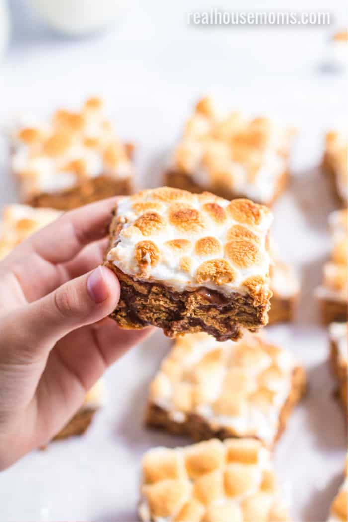 hand holidng a cereal bar topped with toasted marshmallows