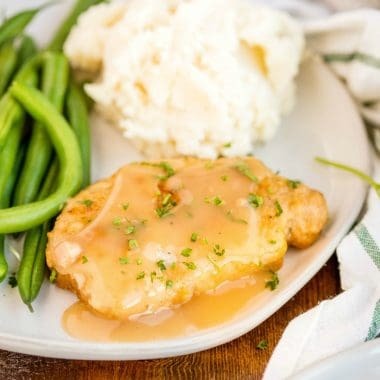 Smothered Fried Pork Chops are classic Southern food! Breaded fried pork chops are smothered in pan gravy and served with your favorite Sunday supper sides!