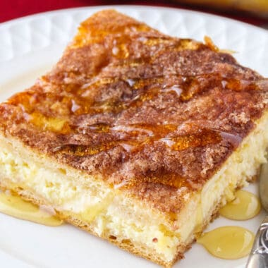 square close up image of a sopapilla cheesecake slice drizzled with honey