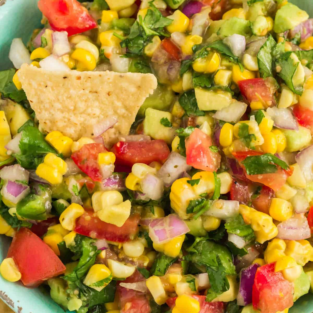 square close up image of southwest corn salsa with a tortilla chip