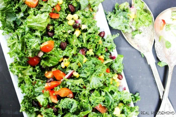 SOUTHWESTERN KALE SALAD is made with a variety fresh vegetables and kale tossed in a cumin vinaigrette for a summer side you can't beat!