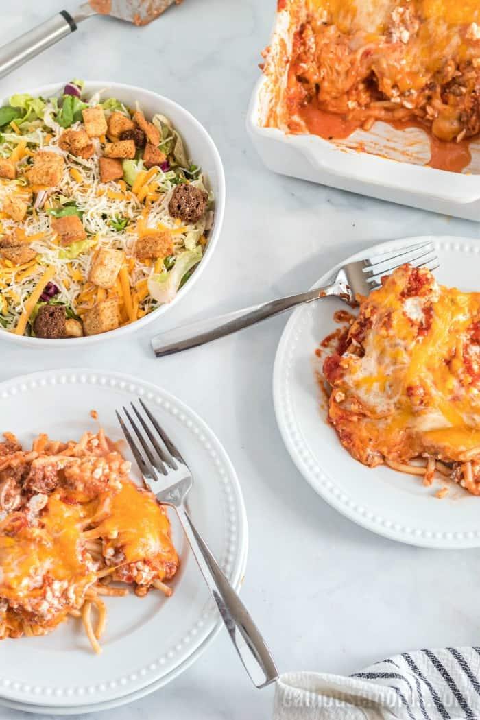 spaghetti casserole on plates with a side salad
