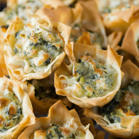 Spanakopita Tarts have all the same great flavor you love in a small grab and pop appetizer! These tarts are elegant enough for the holiday season, and will go perfectly with all your other bite-sized morsels!