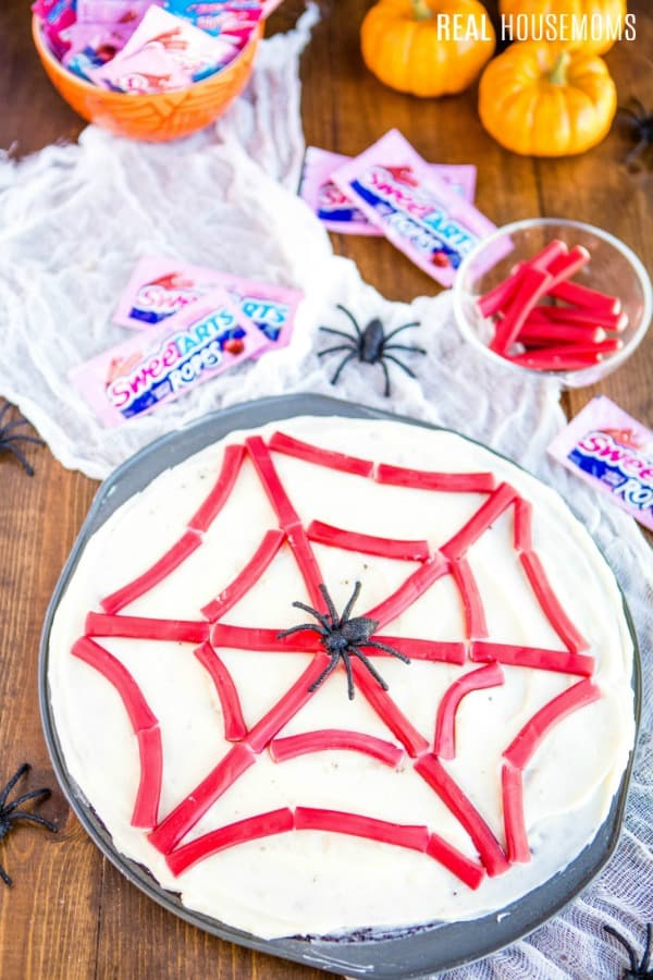 finished spider web brownie pizza with SweeTARTS ropes and plastic spider rings